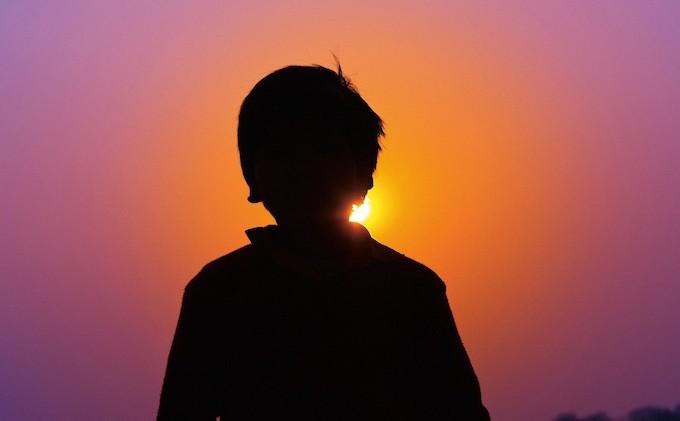 夕陽に向かっている子ども