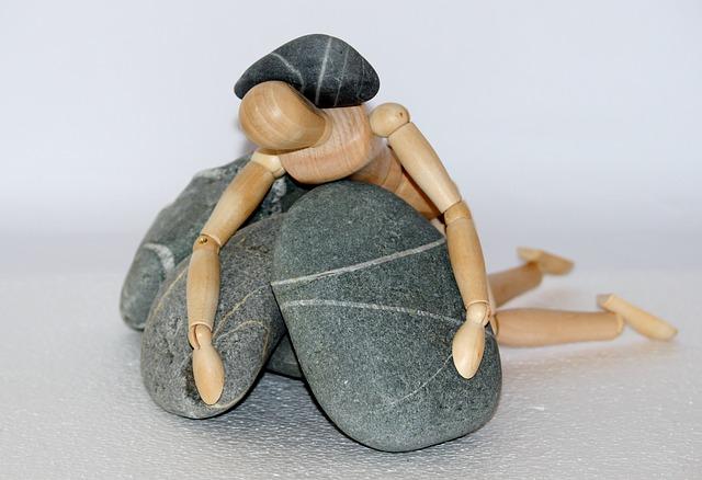石に押し潰される人形