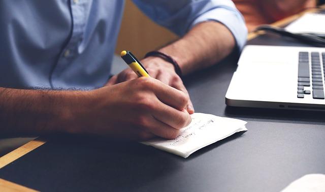 机でメモを書く男性の腕